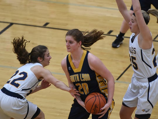South Lyon's Chloe Grimes tries to hang on to the ball