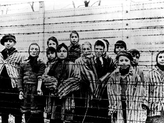 A picture taken just after the liberation by the Soviet army in January, 1945, shows a group of children wearing concentration camp uniforms behind barbed wire fencing in the Oswiecim (Auschwitz) nazi concentration camp in Poland.