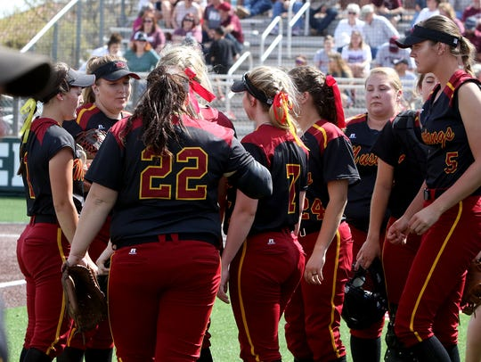 The Midwestern State Mustangs huddle up between innings