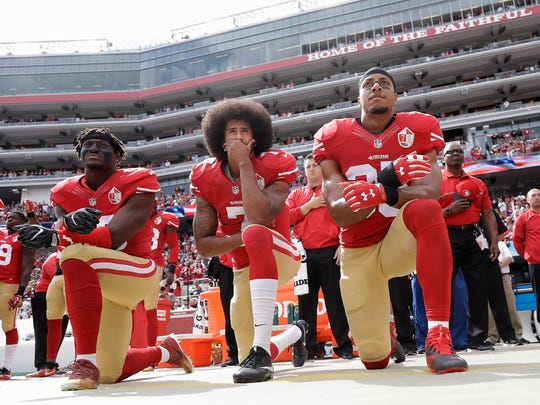From left, San Francisco 49ers outside linebacker Eli Harold, quarterback Colin Kaepernick and safety Eric Reid kneel in protest during the national anthem before a game against the Dallas Cowboys on Oct. 2, 2016.