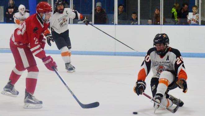 Mamaroneck defenseman Will Payne hits the ice to block a shot in the first period of a 3-1 win over North Rockland on Friday in a Division I semifinal at Hommocks Park Ice Rink.