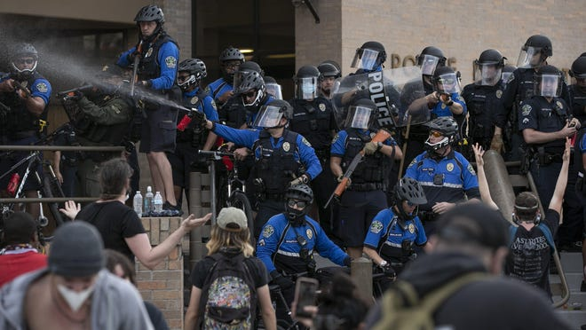 Police and protesters clash at the Austin Police Department's headquarters May 30 during a demonstration after the death of George Floyd in Minneapolis. Protesters threw water bottles at the police, and police responded with pepper spray and other less-lethal devices.