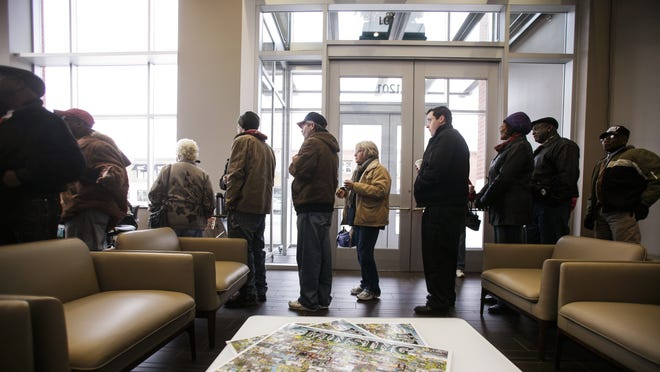 Board of Water & Light customers waited in line on Dec. 30, 2013, at the utility REO Town headquarters, one of the three walk-in centers opened after BWL's outage management system failed to work. BWL officials say they have vastly improved tools for reporting outages.