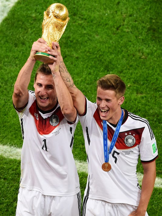 Germany's Miroslav Klose holds up the trophy next to Germany's Erik Durm after the World Cup final soccer match between Germany and Argentina at the Maracana Stadium in Rio de Janeiro, Brazil, Sunday, July 13, 2014. Mario Goetze volleyed in the winning goal in extra time to give Germany its fourth World Cup title with a 1-0 victory over Argentina on Sunday. (AP Photo/Francois Xavier Marit, Pool)