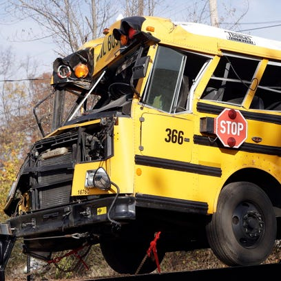 A crashed school bus is carried away on Nov. 22, 2016,