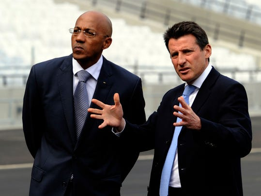 FILE- In this Tuesday, March 29, 2011 file photo,  former Namibian athlete and Chairman of the IOC Athletes' Commission Frank Fredericks, left, listens to former British athlete and head of the LOCOG, Sebastian Coe, right, after laying the final bit of turf in the London 2012 Olympic stadium, London. The International Olympic Committee has suspended Frank Fredericks, Tuesday, Nov. 7, 2017. The decision comes four days after he was charged in a French investigation of suspected bribery in the 2016 Olympic host city vote.  (AP Photo/Tom Hevezi, File)