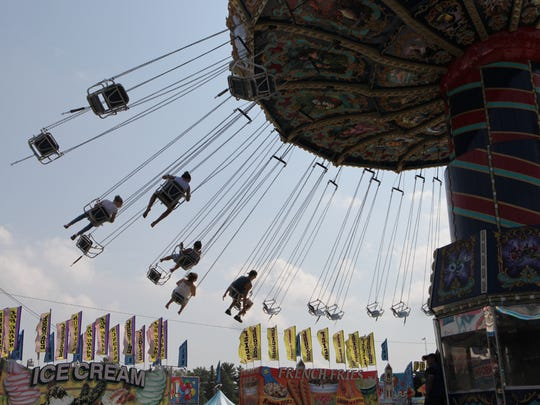 People are silhouetted against the sky as they enjoy the swings at the 172nd Dutchess County Fair in Rhinebeck, Aug, 22, 2017.