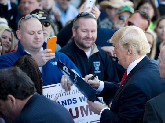 Republican presidential candidate Donald Trump signs autographs during a rally Saturday, Feb. 27, 2016, in Bentonville, Ark.