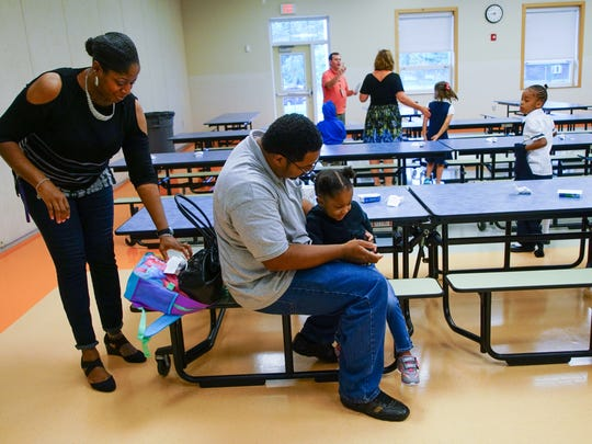 Sonya and Brahyme Moss play in the cafeteria with their 3-year-old daughter Brandy, a preschooler at Charles W. Bush Preschool, during the annual Boo Hoo Breakfast at Hanby Elementary for families who just dropped off their kindergartener on the first day of school.