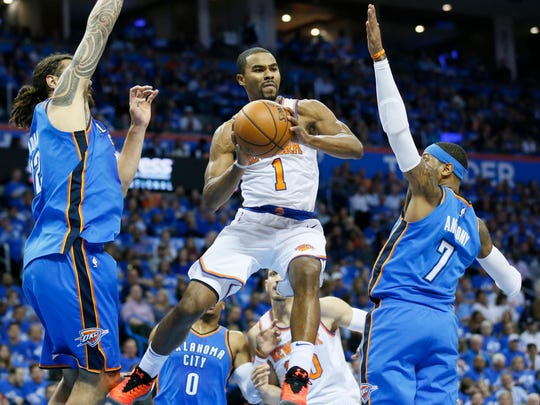 New York Knicks guard Ramon Sessions (1) drives and passes between Oklahoma City Thunder center Steven Adams, left, and forward Carmelo Anthony (7) in the first quarter of an NBA basketball game in Oklahoma City, Thursday, Oct. 19, 2017. (AP Photo/Sue Ogrocki)