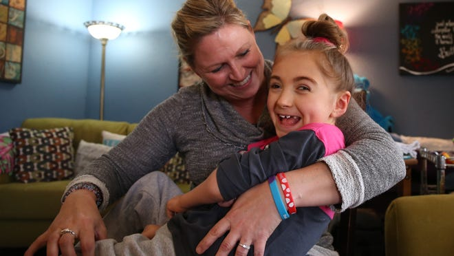 Brenda Hummel laughs with her daughter Andrea, 7, who is disabled by a rare form of epilepsy, in the living room of their Grimes home April 8.