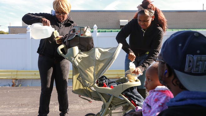 Dewayne Forney of Flint looks on while holding his daughter Vanessa Forney as Anjhe' Walker (center) 14 and Estella Walker (left) mix baby formula using bottled water in the parking lot of a restaurant in downtown Flint on Thursday October 1, 2015 for the children Vanessa and Dewayne Forney Jr.