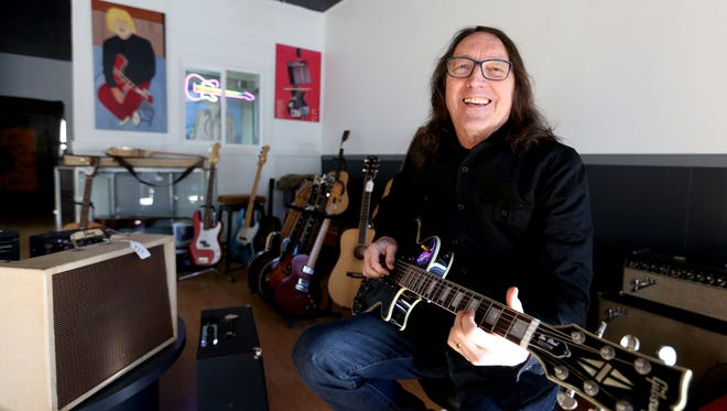 Owner Tim Knight plays a guitar inside the newly opened Guitar Castle in downtown Salem on Ferry Street. The vintage guitar shop has reopened in a new location after a four year hiatus.