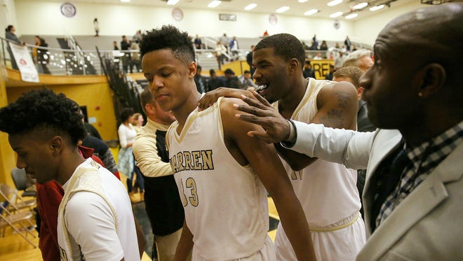Warren Central Warrior Ki-ng Tyler (33) is congratulated after Warren Central won Marion County boys quarterfinals at Warren Central High School, Indianapolis, Wednesday, Jan. 11, 2016. Warren Central defeated Lawrence North, 52-43.
