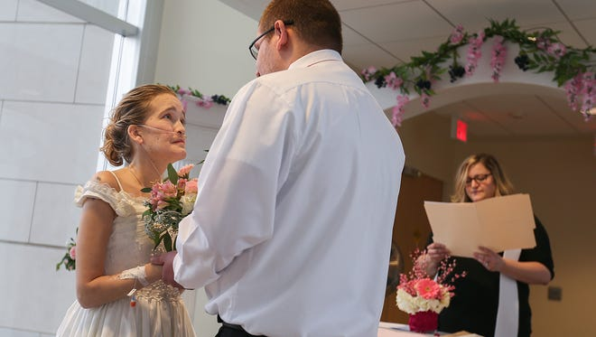 "From left, Hillary and Titus Sears say ""I do,"" as IU Health Chaplain Staci Striegel-Stikeleather officiates at the IU Simon Cancer Center in Indianapolis, Friday, Jan. 27, 2017. Hillary and Titus Sears planned to marry in August, but decided Wednesday to have the wedding as soon as possible since Hillary's cystic fibrosis is causing her health to decline."