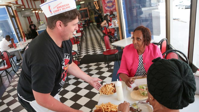 American Coney Island employee Austin Morris brings food for Miriam Ebanks of  Orlando, Florida and Olive Ebanks (right) of Toronto, Ontario at American Coney Island in downtown Detroit on Wed., May 17, 2017.