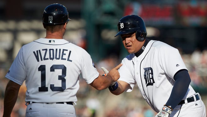Tigers first baseman Miguel Cabrera (24) receives congratulations from first base coach Omar Vizquel (13) after he hits a single in the second inning on Saturday, July 29, 2017, at Comerica Park.
