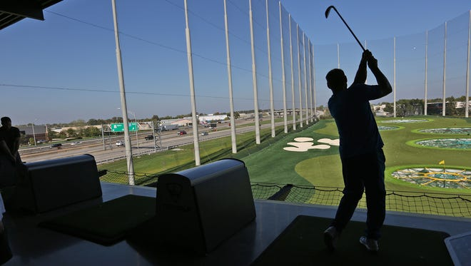Right off I-69, a golfer swings at TOPGOLF in Fishers, Friday, Oct. 13, 2017.
