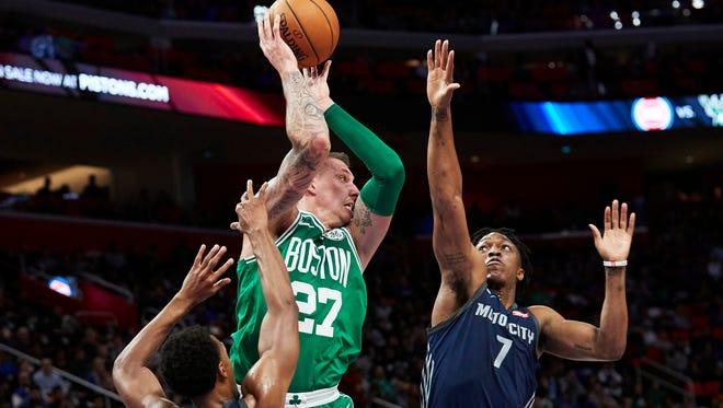 Boston Celtics forward Daniel Theis (27) passes around Detroit Pistons forward Stanley Johnson (7) in the second half at Little Caesars Arena on Friday, Feb. 23, 2018.