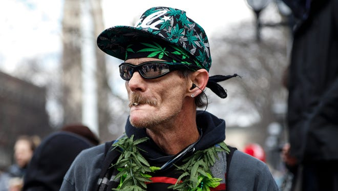 Anthony Hamilton of Wyandotte listens to the speakers as he smokes during the annual Hash Bash at  U-M's Diag in Ann Arbor on Saturday, April 7, 2018.