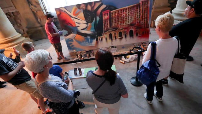 People watch graffiti artist fel3000ft paint in the concourse of Michigan Central Station in Detroit on Saturday, June 23, 2018.