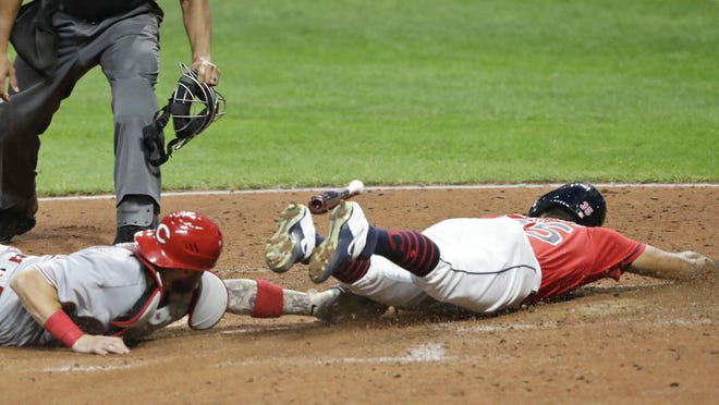 Cleveland Indians' Oscar Mercado, right, slides safely into home plate as Cincinnati Reds' Tucker Barnhart is late on the tag in the fifth inning in a baseball game, Wednesday, Aug. 5, 2020, in Cleveland.