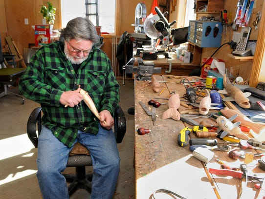 Dennis Bertram carves out a fish decoy Feb. 24 in his