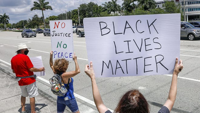 Protesters take part in a peaceful Black Lives Matter rally Saturday near the Mall at Wellington Green at U.S. Route 441 and Forest Hill Boulevard.