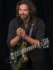 US actor Bradley Cooper plays a guitar as he is filmed