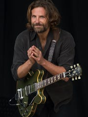 US actor Bradley Cooper plays a guitar as he is filmed