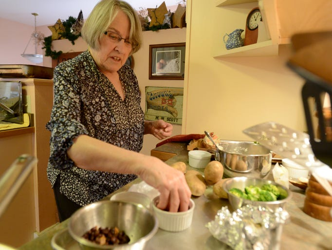 Chef, Linda Hoffman reaches for ingridients as she makes twice-baked potatoes April 1, 2014.