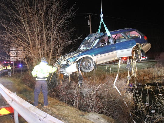 A crew from Lisi's Towing and Recovery lifts a Subaru