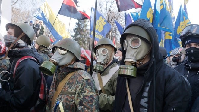 Anti-government protesters look on during clashes with riot police outside Ukraine's parliament in Kiev on Tuesday.