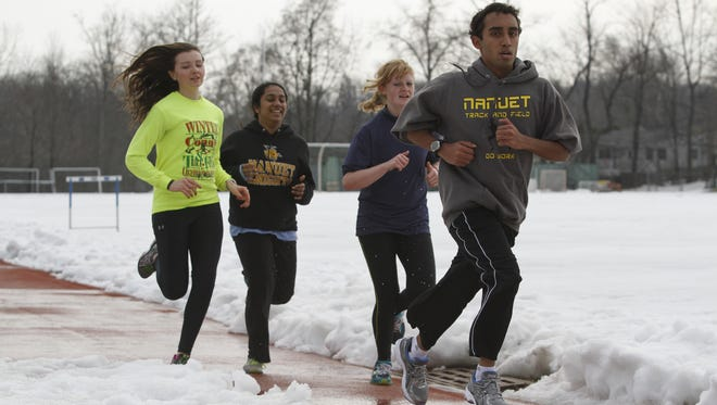 Nanuet track team members Kayla Kiernan, Sanmya George, Amanda Stallone and Ashwin Tanuku run around a partially snow-covered track at Nanuet High School on March 10, 2014.