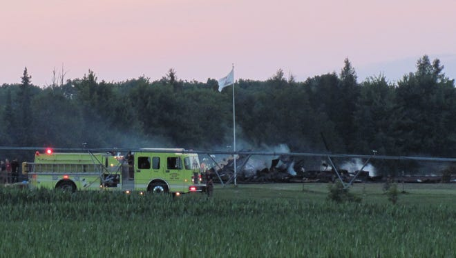 Firefighters work at the scene of a house fire Tuesday night near Rosholt.