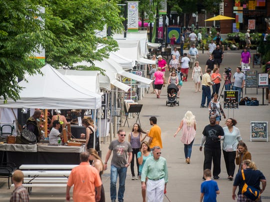 Festival goers browse various art booths at the Dogwood