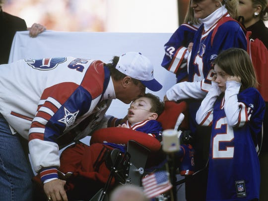Jim Kelly kisses his son Hunter following his induction into the team Wall of Fame at a halftime ceremony on Nov.18, 2001 in Orchard Park.