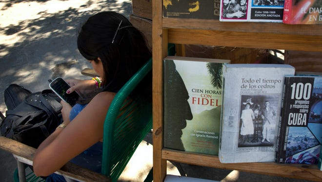 A book street vendor passes the time on her smartphone as she waits for customers in Havana, Cuba. The Obama administration secretly financed a social network in Cuba to stir political unrest and undermine the country's communist government, according to an Associated Press investigation.