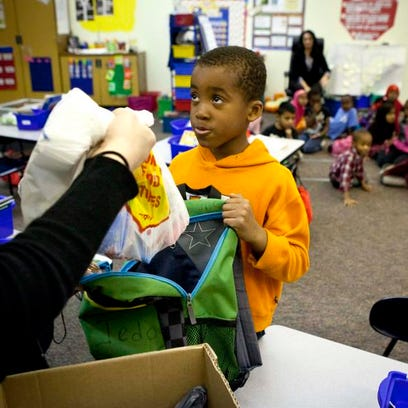 Edmonds Elementary student Samuel Jedo receives a bag of food before leaving school for the weekend from the Food Bank of Iowa's Backpack Buddies program.