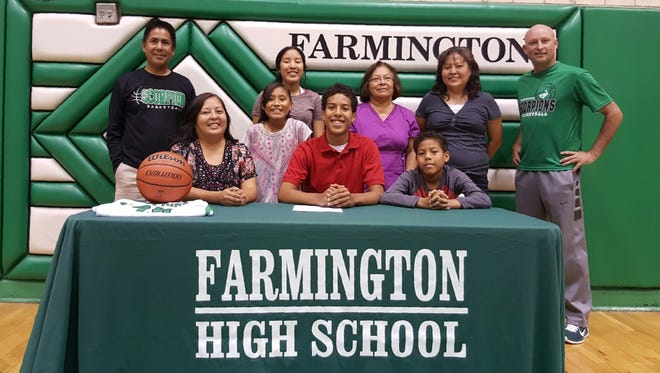 Tyren King signs a letter of intent to play basketball for Little Priest Tribal College on Monday at Scorpion Gym in Farmington.
