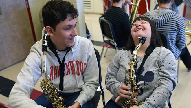 Ravenwood High School student Adam Glick, left, teaches Bethany Steinway how to play the saxophone during school. The school piloted United Sound this fall, a program that teaches special-needs students how to play instruments.