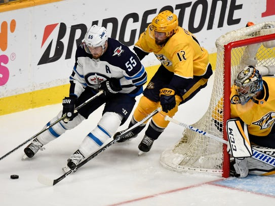 Jets center Mark Scheifele (55) skates with the puck defended by Predators center Mike Fisher (12) behind goaltender Pekka Rinne (35) during the third period of Game 5.