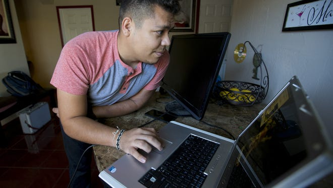 Francisco Luna, 27, tries to fix his computer. Luna was 11 when he came from Mexico to Arizona with his family.