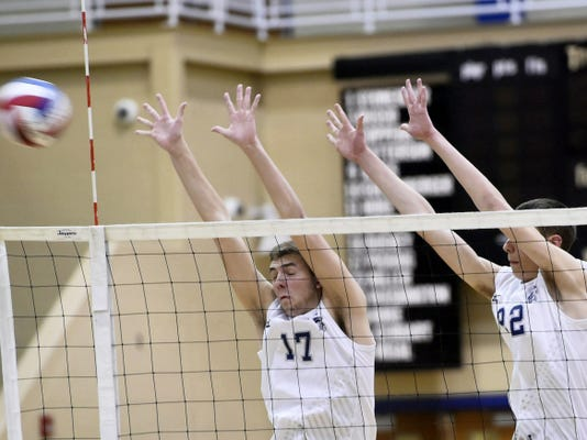 Chambersburg's Brady Picking (17) and Landon Miller (22) try to block a spike from State College on Thursday. The Trojans battled in the third set but lost 28-26 to drop the match 3-0.