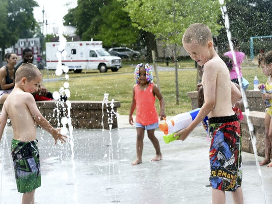 Ian Beksinski, 6, left, Lai'auni Richardson, 4, and Leland Beksinski, 8, play in the splash pad at Mike Waters Park in Chambersburg on Saturday, May 30, 2015.