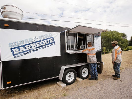 Eric Espinoza, left, and Tony Mitchell wait for their orders Thursday at Silver Star Barbecue in a parking lot near 20th Street and Butler Avenue in Farmington.