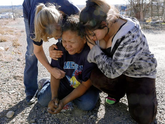 Darleene Tso, middle, cries with neighbors and family members Saturday in front of her home where her son, Myles Roughsurface, was shot and killed Friday by a New Mexico State Police officer in Spencerville.