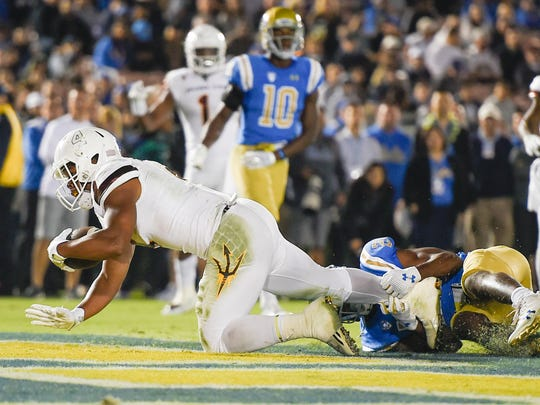 Nov 11, 2017; Pasadena, CA, USA; Arizona State Sun Devils running back Demario Richard (4) runs in a touchdown defended by against the UCLA Bruins during the first half at Rose Bowl. Mandatory Credit: Kelvin Kuo-USA TODAY Sports