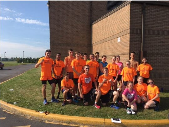 Trevor Garrabrant, center, is the coach of the Crestview cross country team. He's also the vocal music teacher at the high school/middle school and is certified director of the Fun Center Chordsmen.