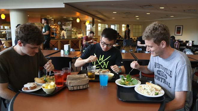 Students Neil Heberer from Rochester Hills, Jun Zhang from China and Dan Steigerwald from Ohio eat lunch at Snyder Hall on the Michigan State campus in East Lansing on Monday, Aug. 22, 2016.
